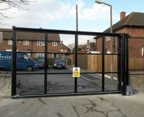 Sliding tracked steel gate clad with mesh